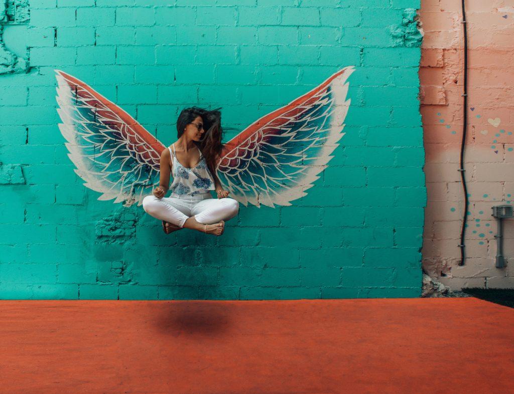 Femme avec des ailes d'ange dessiné sur un mur derrière