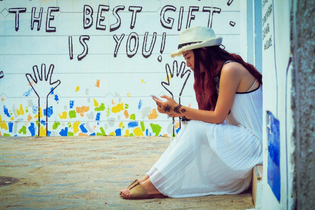 Femme assise sur une marche devant un mur blanc