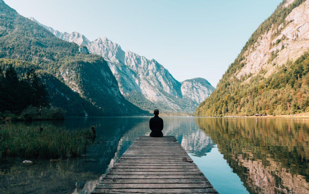 homme devant un lac regardant les montagnes