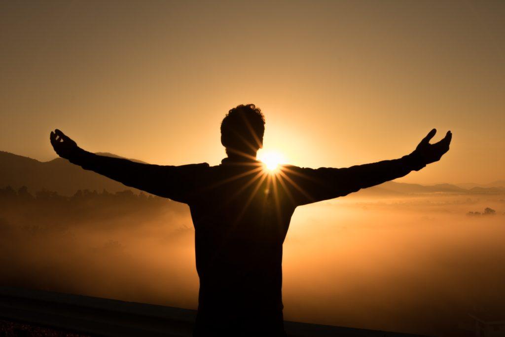 Homme devant le soleil couchant