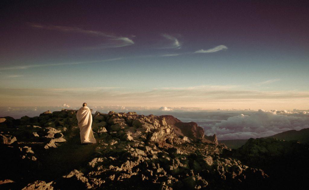 Homme en haut d'une montagne regardant le ciel